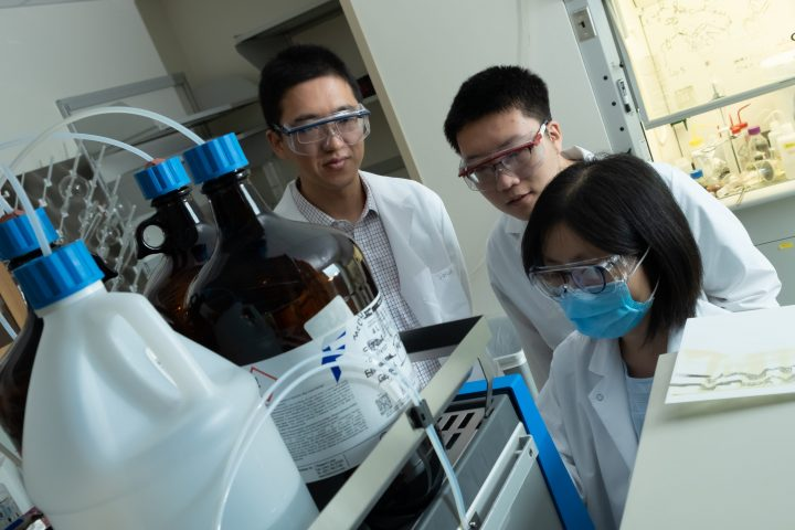 From left, Rice University bioengineer Han Xiao, graduate student Chenfei Yu and postdoctoral researcher Juan Tang monitor a sample in Xiao's lab. The researchers have developed pClick, a new technique to attach drugs or other substances to antibodies. (Credit: Jeff Fitlow/Rice University)