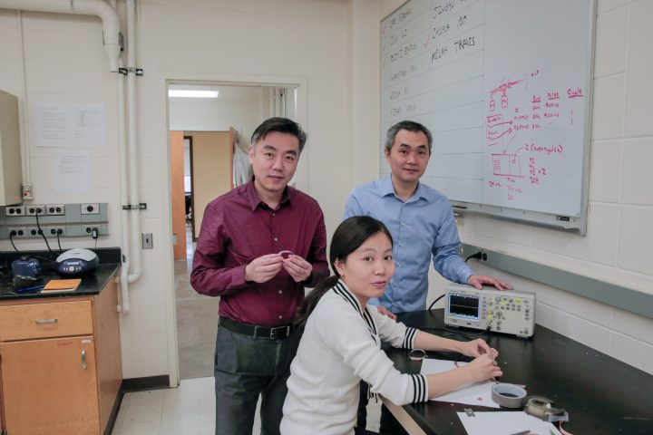 Materials science and engineering professor Xudong Wang, left, holds a prototype wound-healing device that generates energy from body movements. Graduate student Yin Long, seated, and visiting radiology professor Hao Wei collaborated on development of the new device. Image credit: Sam Million - Weaver