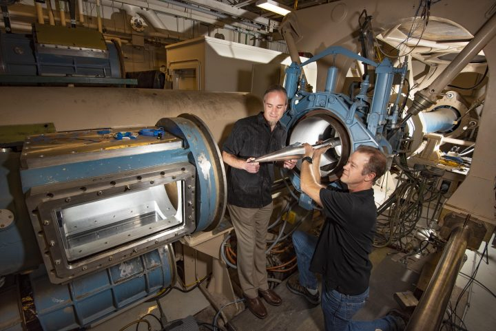 Aerospace engineer Steven Beresh, left, and technologist Russell Spillers of Sandia National Laboratories' aerosciences department place a model in the hypersonic wind tunnel's test section. (Photo by Randy Montoya)