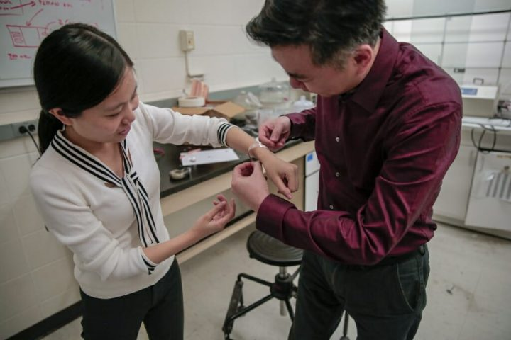 Materials science and engineering professor Xudong Wang fits a new wound dressing around the wrist of graduate student Yin Long. The device stimulates healing using electricity generated from the body's natural motions. Image credit: Sam Million - Weaver