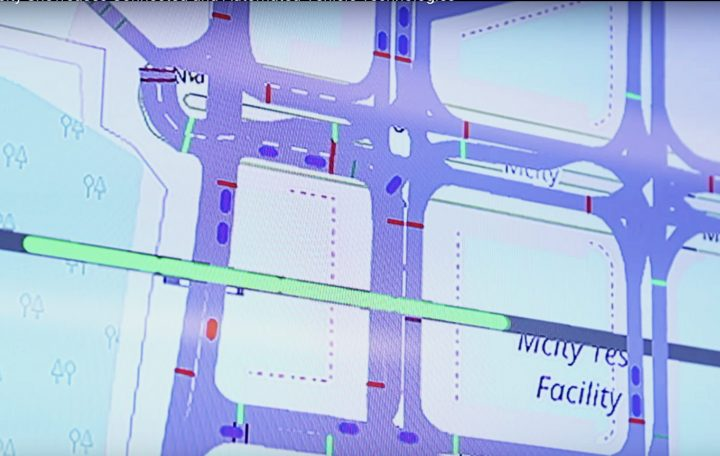 An image of the screen in the Michigan Traffic Lab while a virtual train (in green) travels through a rail crossing at Mcity. Real (red) and simulated vehicles (blue) react. Image credit: Mike Wood, University of Michigan