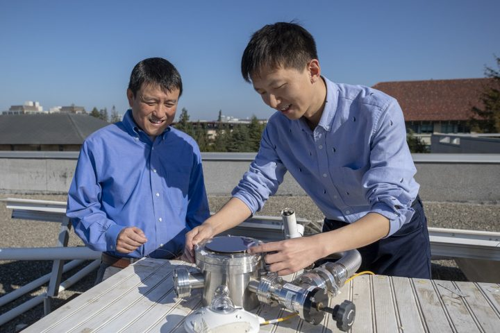 Professor Shanhui Fan and postdoctoral scholar Wei Li atop the Packard Electrical Engineering building with the apparatus that is proving the efficacy of a double-layered solar panel. The top layer uses the standard semiconductor materials that go into energy-harvesting solar cells; the novel materials on the bottom layer perform the cooling task. (Image credit: L.A. Cicero, Stanford University)