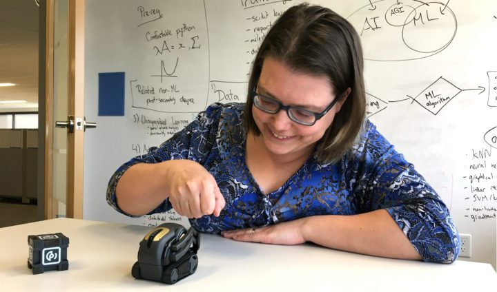 "Anna Koop, director of applied machine learning at the U of A's Alberta Machine Intelligence Institute, gives her Vector AI robot a fist bump. ""I still greet it every morning when I come into the office,"" she says. Image credit: Bev Betkowski / University of Alberta"