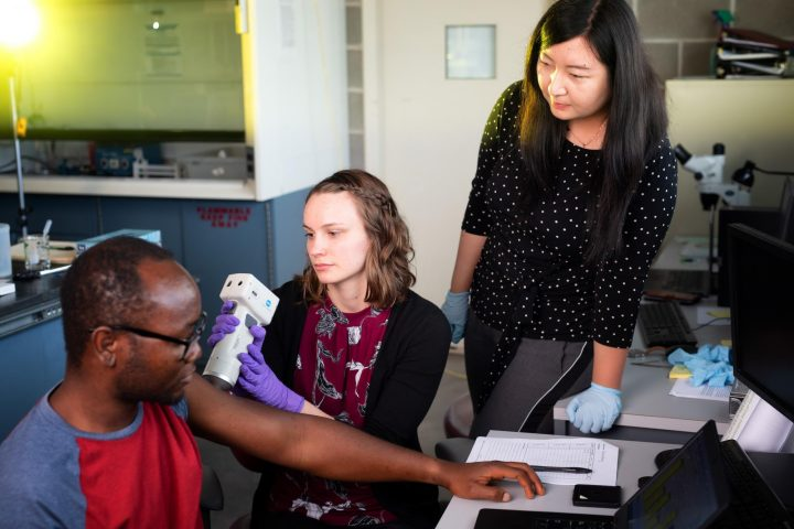 Crissy Lawson, a second-year PharmD student, practices administering tests on Abayomi Ogunjimi, a pharmaceutical science postdoc student, as Xinyi Gao, also pharmaceutical science postdoc looks on. Photo by Justin Torner/University of Iowa