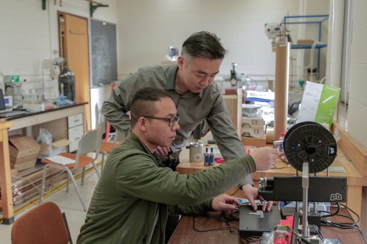 Graduate student Guang Yao (seated) and principal investigator Xudong Wang (standing) make adjustments to a 3D printer that was used to fabricate implantable weight-loss devices. Image credit: Sam Million-Weaver / University of Wisconsin-Madison