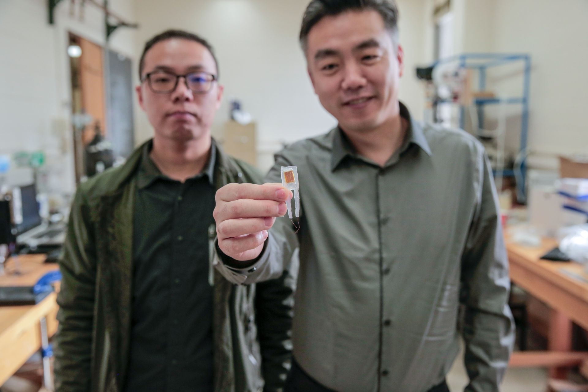 Graduate student Guang Yao (left) and Xudong Wang (right) hold a small implantable device that helped rats lose 40 percent of their body weights. Photo credit: Sam Million-Weaver / University of Wisconsin-Madison