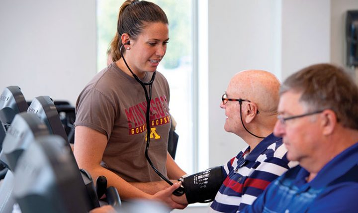 Exercise Interventionist Kaitlin Kelly takes Bruce Erickson's blood pressure to ensure he is exercising at the prescribed level. Image credit: University of Minnesota