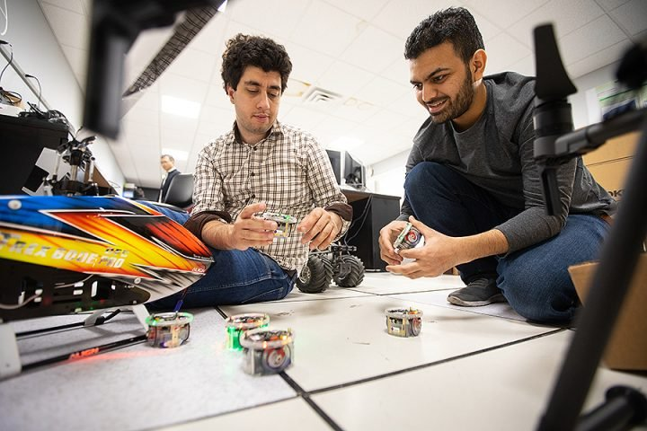 University at Buffalo graduate students work with autonomous vehicles inside the lab of Rahul Rai. Image credit: Douglas Levere, University at Buffalo.