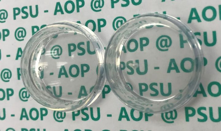 Plastic dome coated with a new antireflection coating (right), and uncoated dome (left). Image credit: Giebnik Lab/Penn State