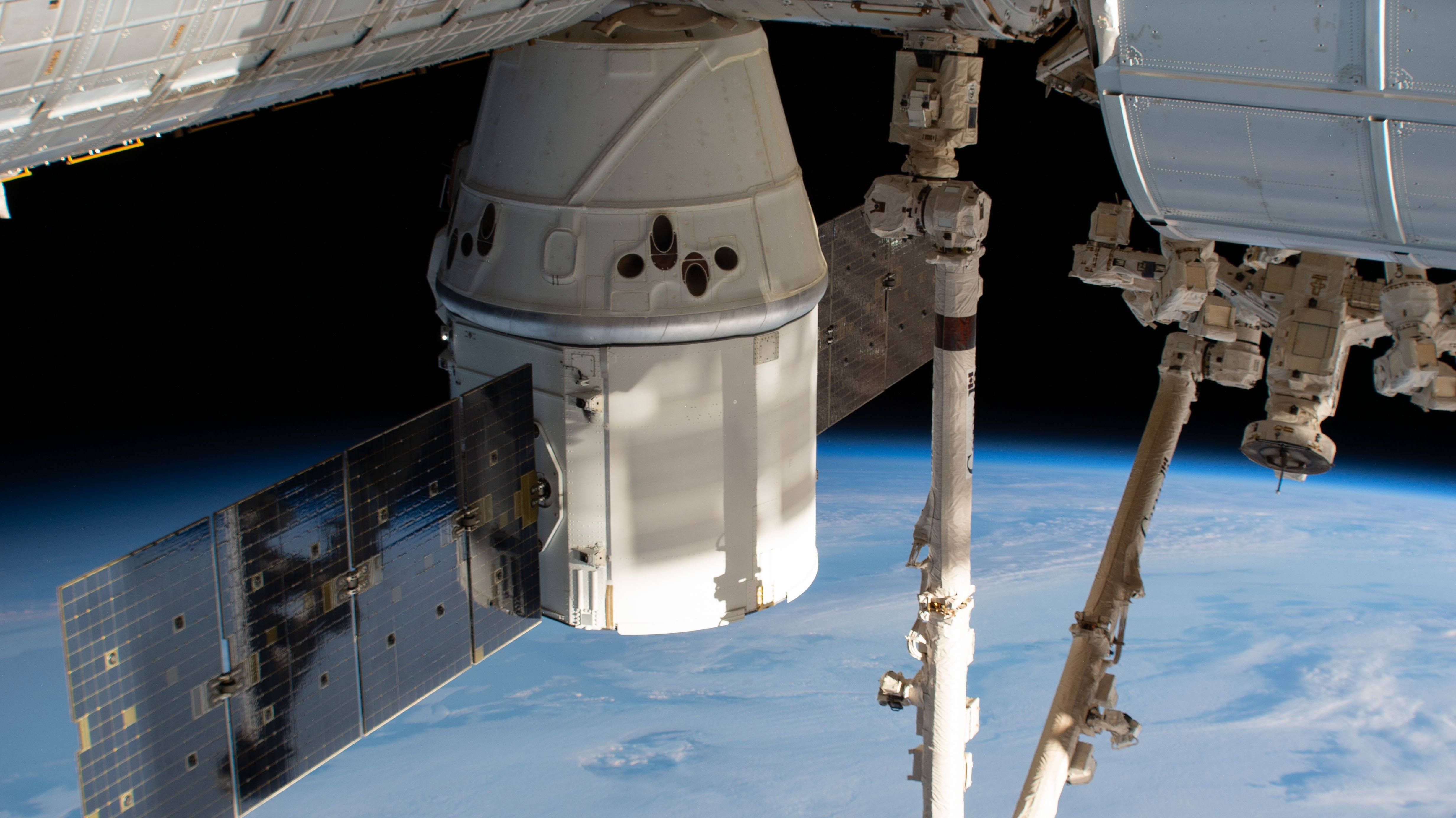 The SpaceX Dragon cargo craft is pictured attached to the International Space Station's Harmony module as the orbital complex orbited 261 miles above the Indian Ocean southwest of the continent of Africa. The Canadarm2 robotic arm vertically splits the frame prior to grappling the spacecraft ahead of planned departure activities. Credits: NASA