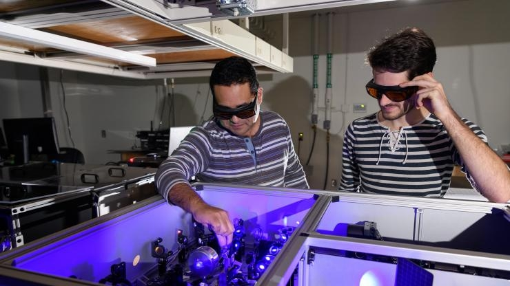 Carlos Silva (l.) in his lab at Georgia Tech with graduate research assistant Félix Thouin examining a setup to process laser light in the visible range for the testing of quantum properties in a halide organic-inorganic perovskite. Image credit: Georgia Tech / Rob Felt