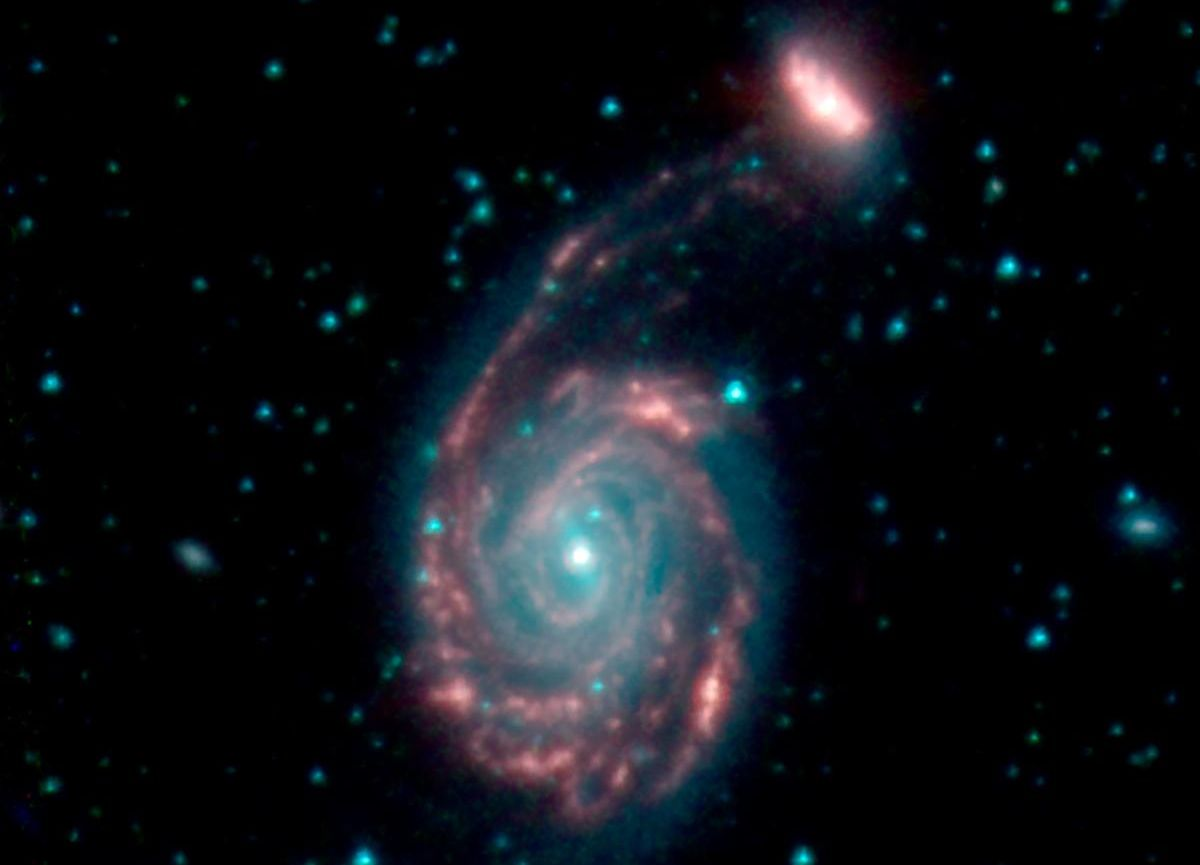 This image shows the merger of two galaxies, known as NGC 7752 (larger) and NGC 7753 (smaller), also collectively called Arp86. In these images, different colors correspond to different wavelengths of infrared light. Blue and green are wavelengths both strongly emitted by stars. Red is a wavelength mostly emitted by dust. Credit: NASA/JPL-Caltech