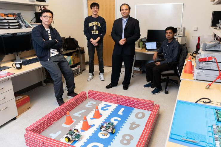 Georgia Tech Researchers Ningyuan Cao, Muya Chang, Arijit Raychowdhury and Anupam Golder with a laboratory demonstration of an ultra-low power hybrid chip driving two small robotic cars. (Photo: Allison Carter, Georgia Tech)