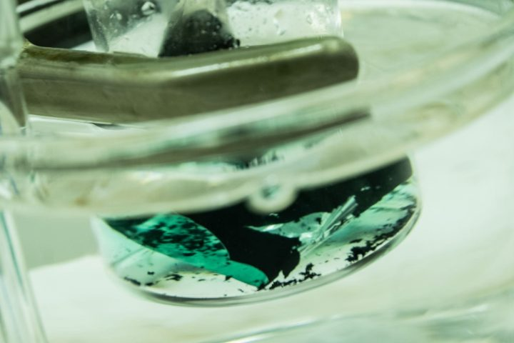 A solution turns green as it pulls cobalt from a spent lithium-ion cathode. A Rice University laboratory is developing an environmentally friendly method to recover valuable metals from used batteries. (Photo by Jeff Fitlow/Rice University)