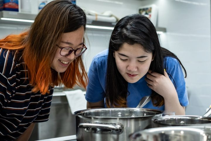 """Rice University freshmen Minjung Kim, left, and So Jeong (Brianna) Lee cook a batch of coconut """"mylk"""" in Rice's research kitchen. A class of students worked with an alumnus to refine a recipe for the vegan product. (Credit: Jeff Fitlow/Rice University)"""