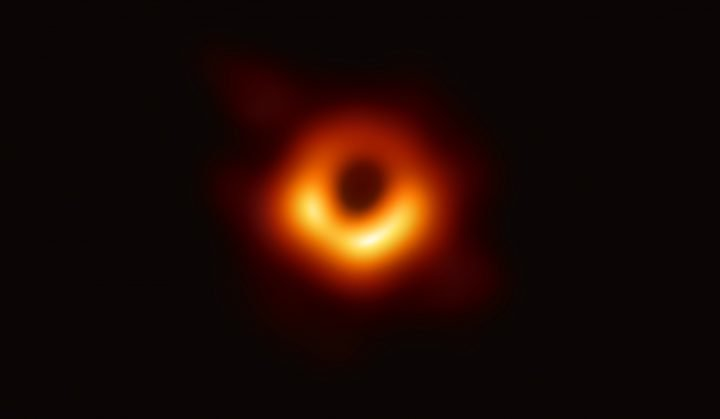 Using the Event Horizon Telescope, scientists obtained an image of the black hole at the center of galaxy M87, outlined by emission from hot gas swirling around it under the influence of strong gravity near its event horizon. Image credit: Event Horizon Telescope collaboration et al.