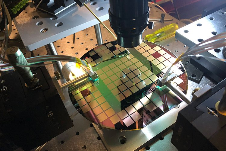 """The photonic switch is manufactured using a technique called photolithography, in which each """"light switch"""" structure is etched into a silicon wafer. Each light gray square on the wafer contains 6,400 of these switches. Image credit: Kyungmok Kwon"""