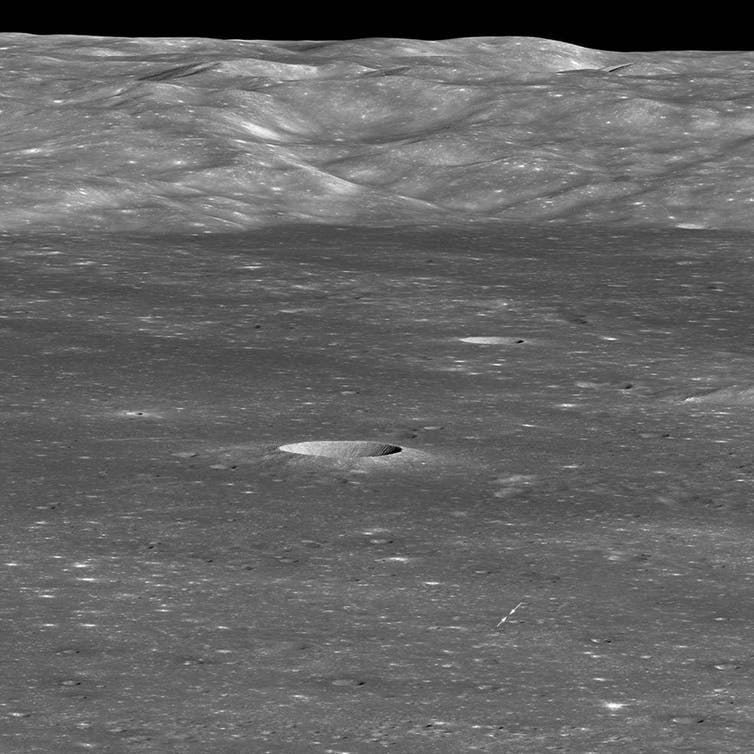 Arrows indicate position of Chang'e 4 lander on the floor of the Moon's Von Kármán crater. The sharp crater behind and to the left of the landing site is 12,800 feet across and 1,970 feet deep. Image credit: NASA/GSFC/Arizona State University, CC BY
