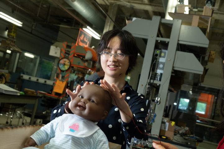 Rice University senior engineering student Sammi Lu attaches a sensor to a mannequin to test a noninvasive system designed to monitor intracranial pressure in infants. (Credit: Jeff Fitlow/Rice University)