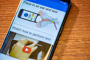 The phone app shows users how to conduct the diagnostic test for ear fluid.