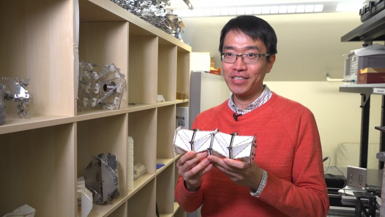 Jinkyu Yang and the paper model. Image credit: Kiyomi Taguchi/University of Washington