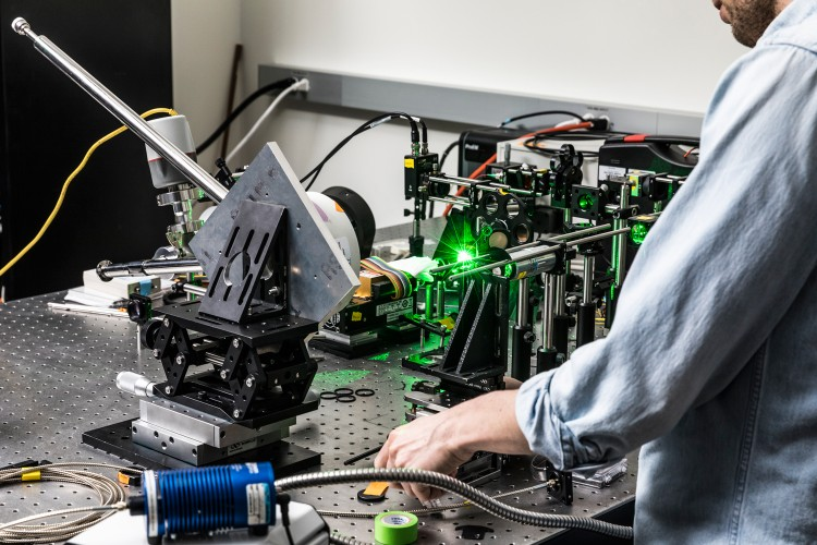 UW postdoctoral researcher Matthew Crane operates equipment that uses a laser to heat the gasket of a high-pressure diamond anvil cell above 3,100 F, more than one-third the temperature of the sun. Image credit: Mark Stone/University of Washington