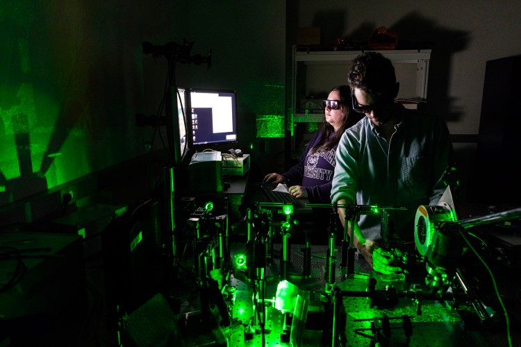 UW researchers Abbie Ganas and Matthew Crane operate equipment that employs a laser to heat the gasket of a high-pressure diamond anvil cell above 3,100 F, more than one-third the temperature of the sun. Image credit: Mark Stone/University of Washington