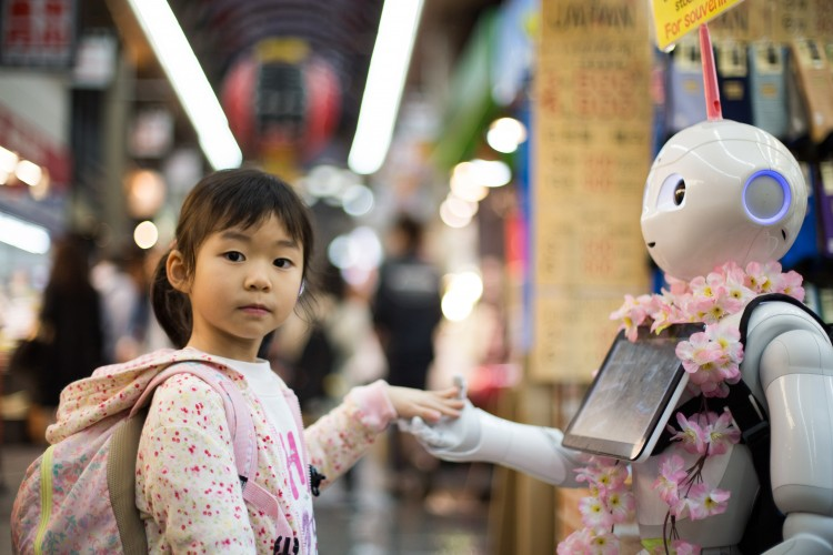 A little girl, making friends with a robot. Image credit: Andy Kelly via Unsplash (Unsplash licence)