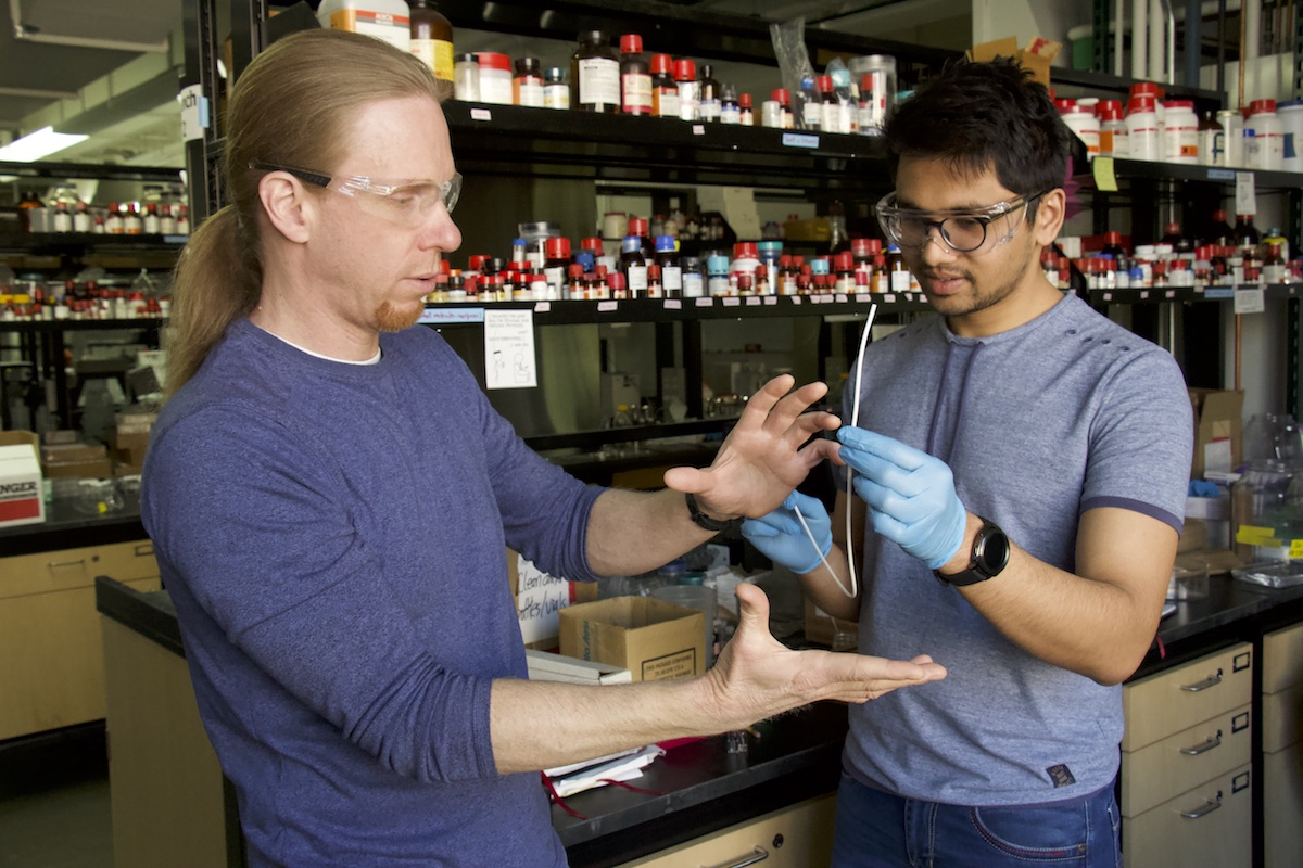 David Lynn, left, a professor of chemical and biological engineering at the University of Wisconsin–Madison, and graduate student Harshit Agarwal discuss the super-slippery coatings they are developing to reduce bacterial growth on implanted medical devices, such as catheters. Photo credit: David Tenenbaum, University of Wisconsin-Madison