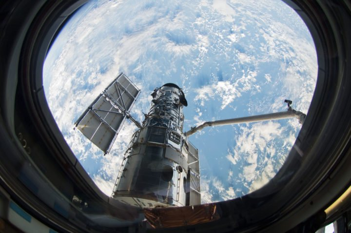 A window on the space shuttle Atlantis frames Hubble as astronaut Megan McArthur uses the shuttle's robot arm to grab the telescope in preparation for the final servicing mission. From its perch 340 miles above Earth, the famed space telescope has tracked celestial objects across the universe. Credits: NASA