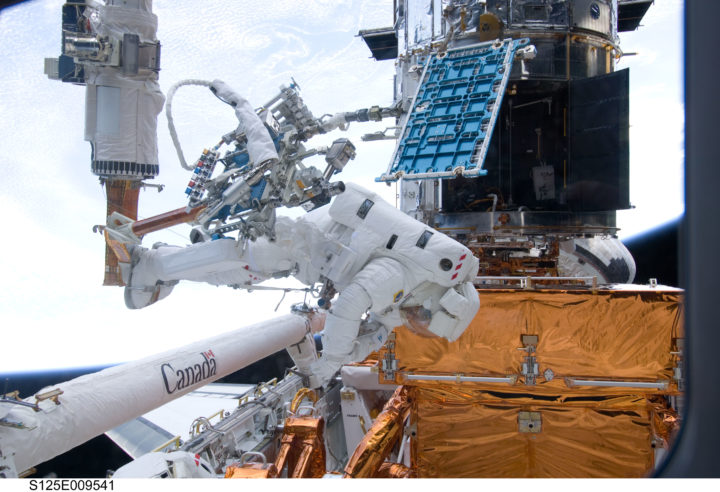 During the mission's fourth spacewalk, Michael Good and Michael Massimino faced a curious challenge: a stripped screw delayed the removal of a handrail (pictured inside the telescope to the upper right of Good's helmet in this photo) on the outside of the Space Telescope Imaging Spectrograph (STIS). After nearly four hours of troubleshooting, Good, Massimino, the rest of the crew and a team back on Earth found a way to remove the handrail and continue the mission. Credits: NASA