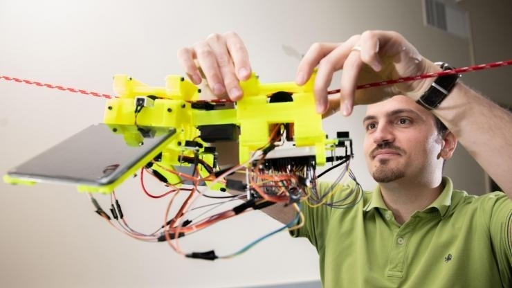 Graduate Research Assistant Gennaro Notomista shows the components of SlothBot on a cable in a Georgia Tech lab. The robot is designed to be slow and energy efficient for applications such as environmental monitoring. Image credit:: Allison Carter, Georgia Tech
