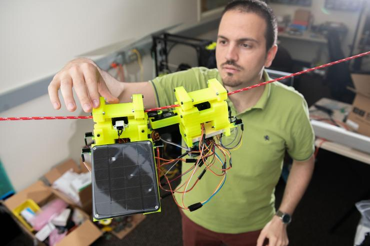 Graduate Research Assistant Gennaro Notomista shows the components of SlothBot on a cable in a Georgia Tech lab. The robot is designed to be slow and energy efficient for applications such as environmental monitoring. (Photo: Allison Carter, Georgia Tech)
