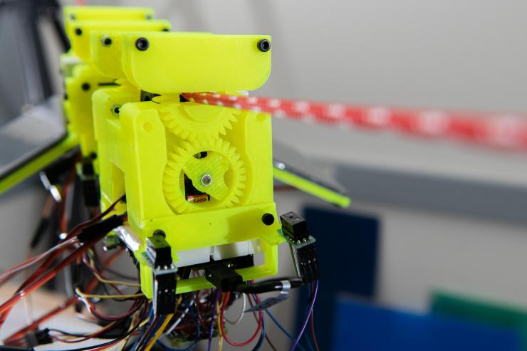 Image shows components of the SlothBot, which is powered by two photovoltaic panels. 3D-printed gears and switches help the robot switch from one cable to another. (Photo: Allison Carter)