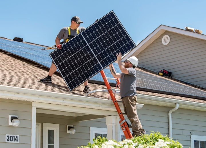 A photovoltaic (solar) panel is being installed on a roof. Image credit: U.S. Air Force/Roland Balik (Public Domain)