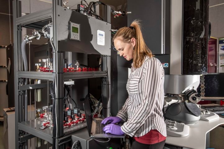 Sandia National Laboratories researcher Katherine Jungjohann, principal investigator and lead microscopist for a study that pinpointed a major cause of corrosion in pipelines, looks for corrosion with a new transmission electron microscope at the Center for Integrated Nanotechnologies. The gas valves on the shelves at left produce different testing environments. (Photo by Randy Montoya)