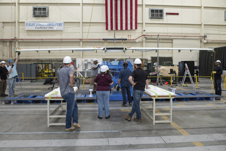 Engineers and specialists prepare X-57s Mod III wing for testing in the Flight Loads Laboratory at NASA's Armstrong Flight Research Center in Edwards, California. Here, the wing began preparation for several tests, including weight and balance measurement, ground vibration testing, and wing loading tests. The high-aspect ratio wing contains 40 percent the area of the Mod II vehicle's baseline wing, and will feature repositioning the two large electric cruise motors out to the wingtips to help boost efficiency. Credits: NASA Photo / Ken Ulbrich
