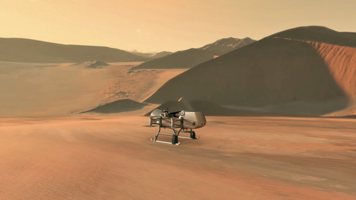 This illustration shows NASA's Dragonfly rotorcraft-lander approaching a site on Saturn's exotic moon, Titan. Taking advantage of Titan's dense atmosphere and low gravity, Dragonfly will explore dozens of locations across the icy world, sampling and measuring the compositions of Titan's organic surface materials to characterize the habitability of Titan's environment and investigate the progression of prebiotic chemistry. Credits: NASA/JHU-APL
