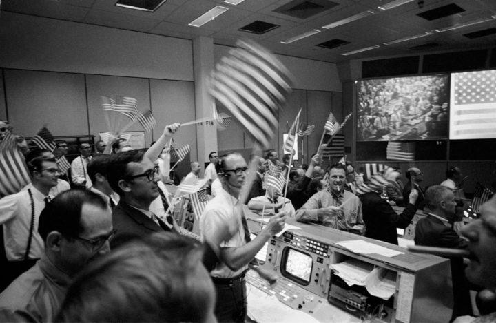 Overall view of the Mission Operations Control Room in the Mission Control Center at the Manned Spacecraft Center showing the flight controllers celebrating the successful conclusion of the Apollo 11 lunar landing mission on Jul 24, 1969. Image credits: NASA