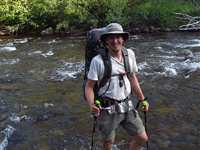 Researcher Nicholas Sutfin crossing St. Vrain Creek, a 32-mile-long tributary of the South Platte River in north central Colorado.
