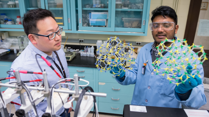 Graduate student Eric Lee, left, and Argonne materials scientist Vineeth Kumar Gattu, right, discuss the molecular structures of metals used in medical device implants. (Image by Argonne National Laboratory.)