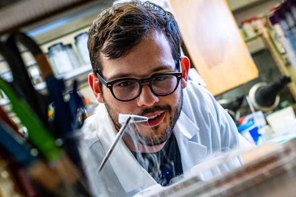 Rice University graduate student Ian Campbell pulls a vial of ferredoxin proteins from cold storage. The iron and sulfur proteins, believed to be present at the start of life on Earth, facilitate the transfer of energy in cells. The Rice experiments showed synthetic biologists may use them to control electron transfer in cells. Illustration by Jeff Fitlow/Rice University
