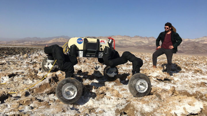 RoboSimian can walk on four legs, crawl, move like an inchworm and slide on its belly. In this photo it stands on the Devil's Golf Course in Death Valley, California, for field testing with engineer Brendan Chamberlain-Simon.Credit: NASA/JPL-Caltech