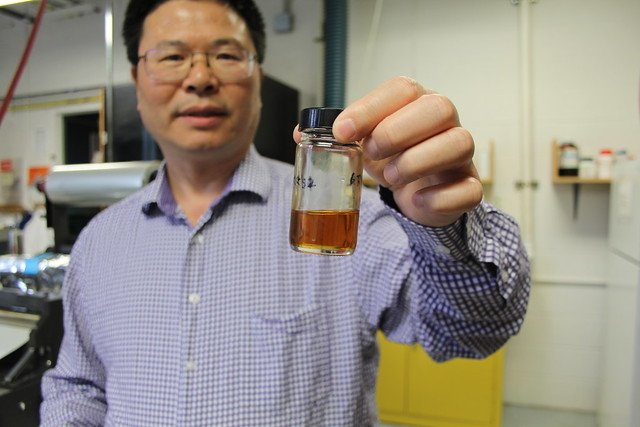 Kaichang Li of Oregon State University holding a container with a vegetable oil-based adhesive he developed. Image credit: Oregon State University via Flickr, CC BY-SA 2.0
