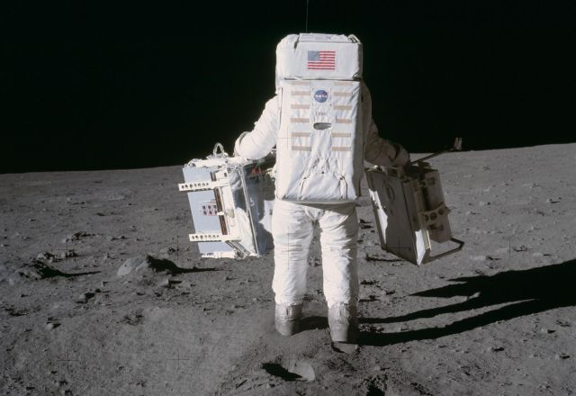 Astronaut Edwin E. Aldrin Jr. moves toward a position to deploy two components of the Early Apollo Scientific Experiments Package (EASEP) on the surface of the Moon during the Apollo 11 extravehicular activity. The Passive Seismic Experiments Package (PSEP) is in his left hand; and in his right hand is the Laser Ranging Retro-Reflector (LR3). Astronaut Neil A. Armstrong, commander, took this photograph with a 70mm lunar surface camera. Credit: NASA