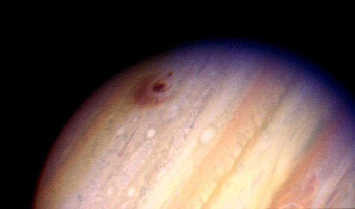 "This image of the giant planet Jupiter, by NASA's Hubble Space Telescope, reveals the impact sites of fragments ""D"" and ""G"" from Comet Shoemaker-Levy 9. The large feature was created by the impact of fragment ""G"" on July 18, 1994 at 3:28 a.m. EDT. It entered Jupiter's atmosphere from the south at a 45-degree angle, and the resulting ejecta appears to have been thrown back along that direction. The smaller feature to the left of the fragment ""G"" impact site was created on July 17, 1994, at 7:45 a.m. EDT by the impact of fragment ""D"". Credits: H. Hammel, MIT and NASA"