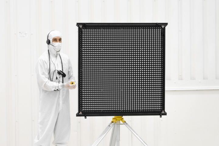 Engineer Chris Chatellier stands next to a target board with 1,600 dots. The board was one of several used on July 23, 2019, in the Spacecraft Assembly Facility's High Bay 1 at NASA's Jet Propulsion Laboratory in Pasadena, California, to calibrate the forward-facing cameras on the Mars 2020 rover. Credit: NASA/JPL-Caltech.
