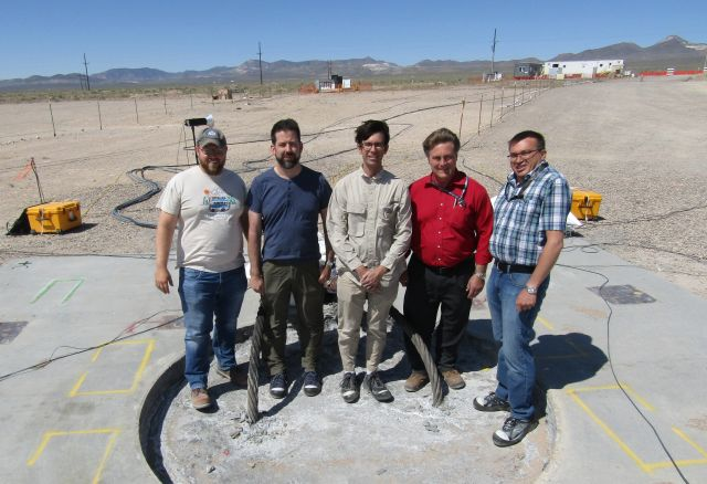 Sandia National Laboratories researchers, from left, Zack Cashion, Rob Abbott, Danny Bowman, Mark Timms and Austin Holland stand on an 8-foot diameter hole filled with gravel, sand, cement and explosives prior to an underground explosion this summer. (Photo courtesy of Sandia National Laboratories)