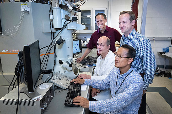 Brookhaven Lab scientists Myung-Geun Han (sitting front), Ivan Bozovic (sitting back), Yimei Zhu (standing back), and Anthony Bollinger of the Condensed Matter Physics and Materials Science Division built electronic transport devices that sandwich a thin layer of an insulating material in between two thicker layers of superconducting materials. They characterized these devices using an electron microscope (seen in background). In collaboration with scientists at Rice University and the University of Connecticut, the team discovered that a high percentage of electron pairs—which are known to carry superconducting current—exists well above expected temperature and energy ranges in a material that conducts electricity without energy loss at unusually high temperatures.
