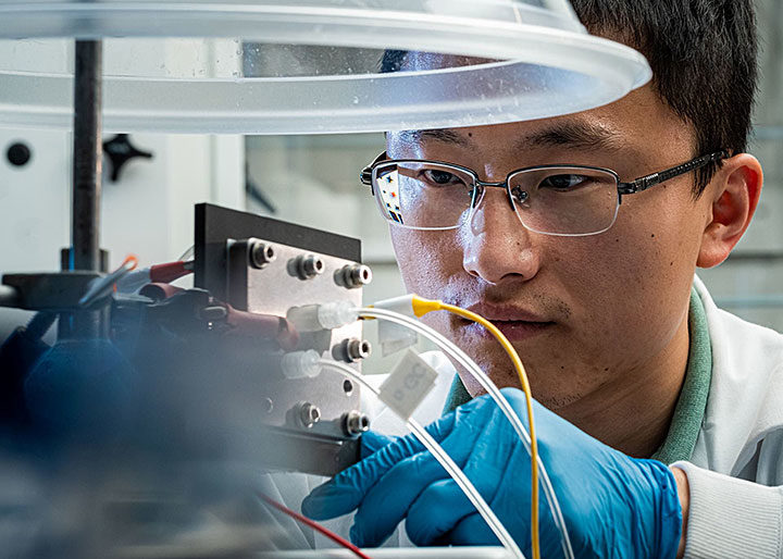 Rice University engineer Haotian Wang adjusts the electrocatalysis reactor built in his lab to recycle carbon dioxide to produce liquid fuel. The reactor is designed to be an efficient and profitable way to reuse the greenhouse gas and keep it out of the atmosphere. (Credit: Jeff Fitlow/Rice University)